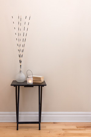 little table: Home decor. Little table decorated with candlelight, vase and books. Stock Photo