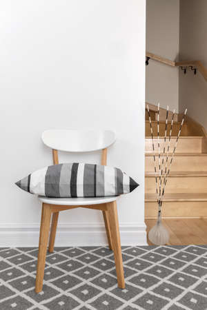 white wood floor: Chair decorated with gray striped cushion in a room with staircase