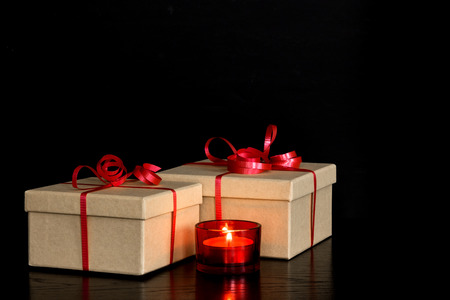 Simple elegant presents and red candlelight on dark background  photo