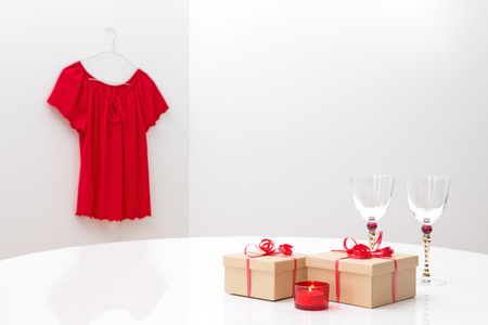 Presents, glasses and candlelight on a table, and red blouse on a hanger  photo