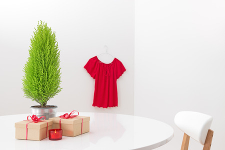 Little Christmas tree and gifts on the table, and red blouse hanging on the wall  photo