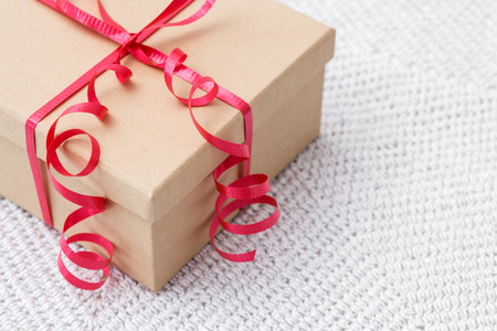 Simple gift box with red ribbon on a knitted background  photo