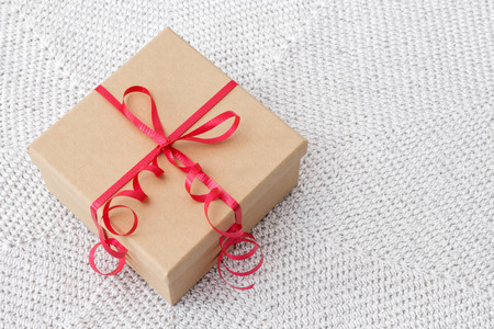 Simple present with red ribbon on a knitted background  photo