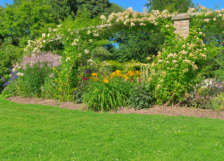Sunny summer garden with green lawn and stone arc  photo