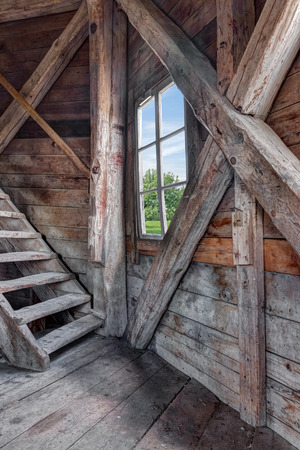 Interior of an abandoned wooden house with staircase and view over green garden  Editorial