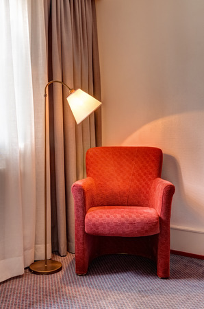 floor lamp: Red armchair and floor lamp in the corner of the room