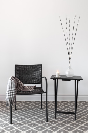 Home decor  Black armchair and little table decorated with decorations  Stock Photo