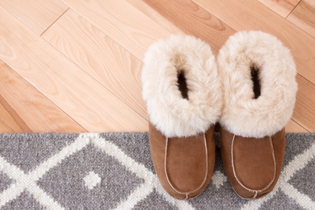 chamois leather: Gray rug and warm slippers on wooden floor  Stock Photo