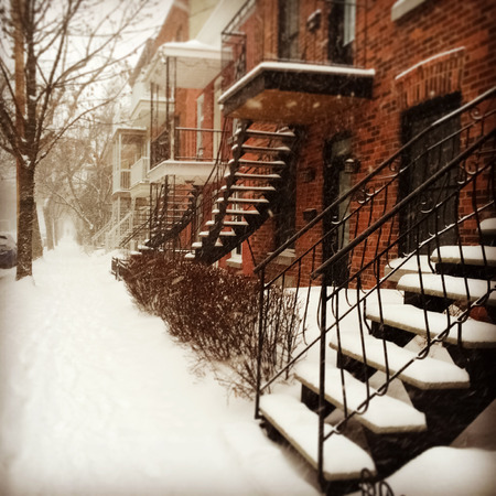 Sudden snowstorm in Montreal  Red brick buildings with staircases covered by snow  photo