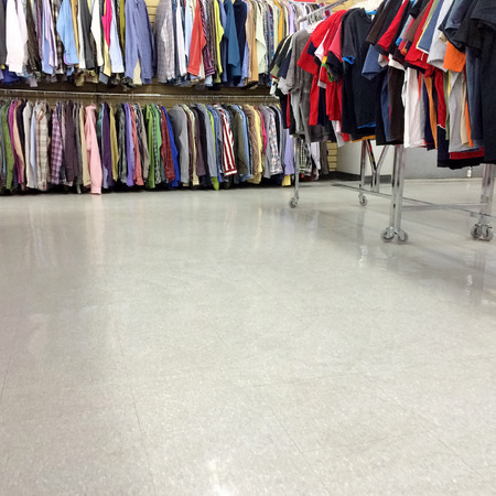 second floor: Colorful clothes for sale in a second hand store, with empty floor as copy space  Stock Photo