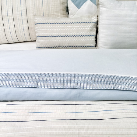 bedclothes: Bed with elegant blue bed linen and pillows.