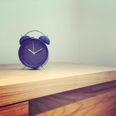 decor: Home decor  Blue alarm old-fashioned clock on wooden furniture  Stock Photo