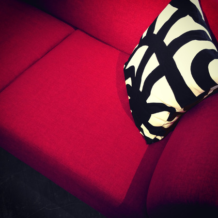 red sofa: Modern red sofa with decorative black and white cushion  Stock Photo