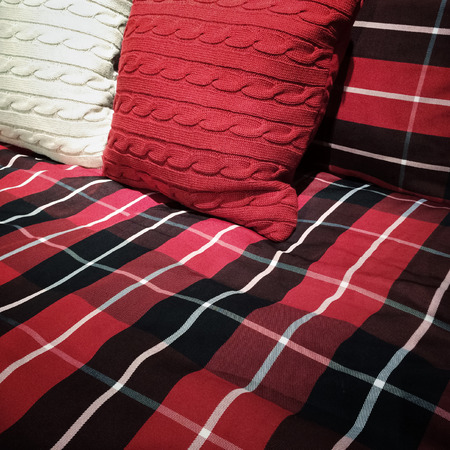bedclothes: Checked bed clothing with red and white cushions  Stock Photo