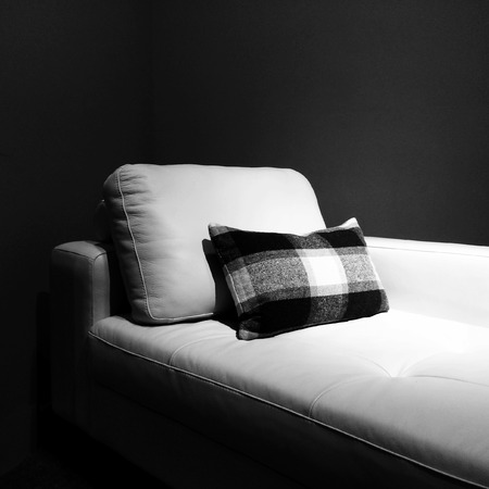 lounge room: White leather couch in a dark room, under the light  Stock Photo
