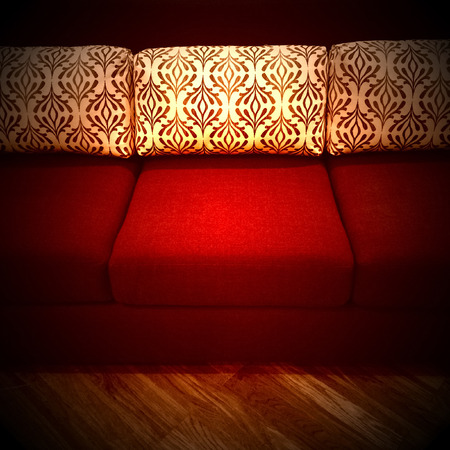 red sofa: Red sofa with decorative cushions in a dark room