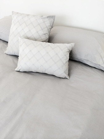 bed sheet: Bed with grey bed linen and pillows  Stock Photo