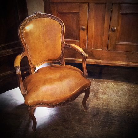 old furniture: Vintage leather chair in a room with old furniture  Stock Photo