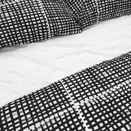 bedlinen: Bed with black and white checked bed linen and pillows