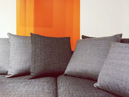 sofa: Close-up of modern gray fabric sofa with cushions.