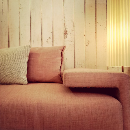 floor lamp: Old fashioned pink sofa with cushions and floor lamp.