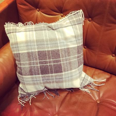 brown leather sofa: Close-up del divano in pelle marrone con cuscino controllato.