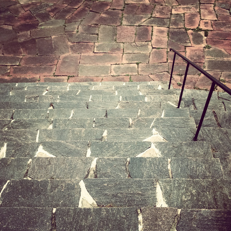 Old stone steps leading down to the tiled square. photo