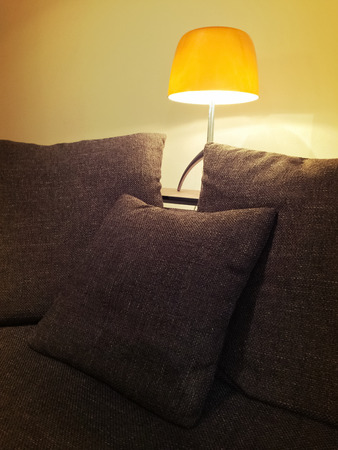 home  lighting: Cozy orange lamp and comfortable sofa in the living room.