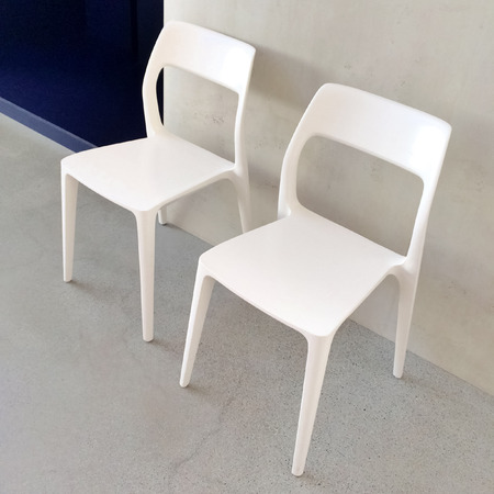 White chairs near the wall, modern design. photo