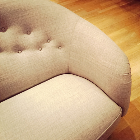 Detail of a fashionable sofa on wooden floor. photo