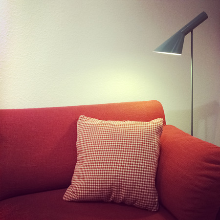 Detail of a living room red sofa and lamp. Modern furniture.
