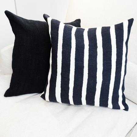 sofa: Striped cushion on a white sofa. Modern furniture. Stock Photo