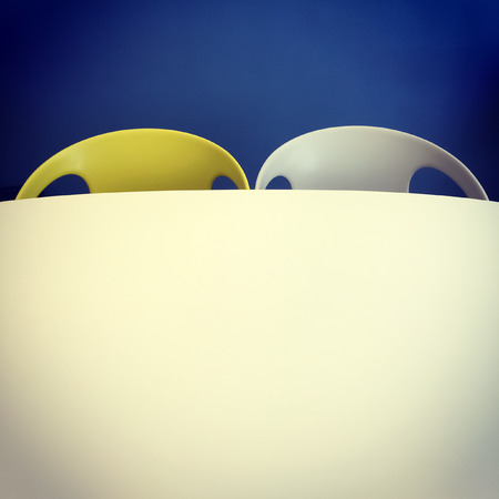 Retro style chairs and table near blue wall. photo