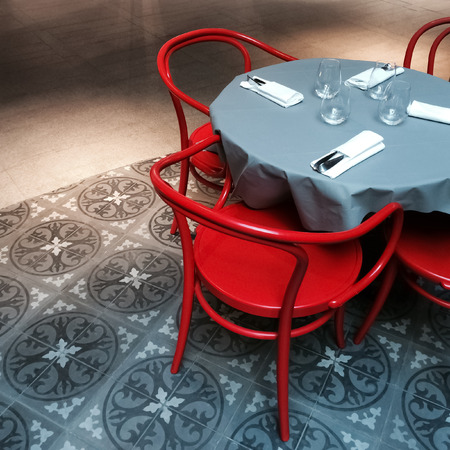 round chairs: Interior with round dining table and red chairs. Stock Photo