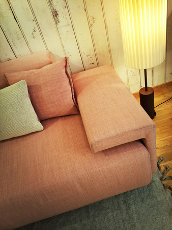 floor lamp: Retro style pink sofa with cushions and floor lamp. Stock Photo
