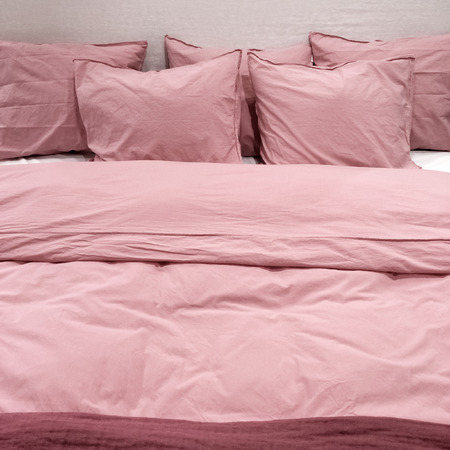 bedclothes: Bed with pink bedclothes and lots of pillows.