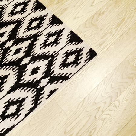 oriental rug: Black and white rug with ethnic design on wooden floor.