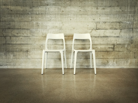 industrial: White chairs near concrete wall, modern industrial design. Stock Photo