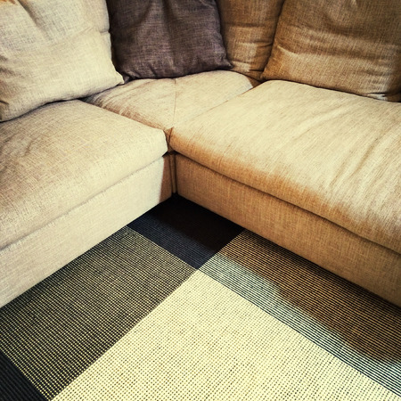 sofa: Textile corner sofa and carpet. Modern furniture.
