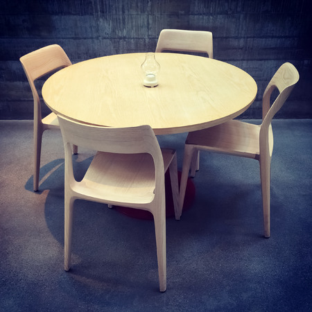 round chairs: Wooden table and chairs in a dark room. Modern design.