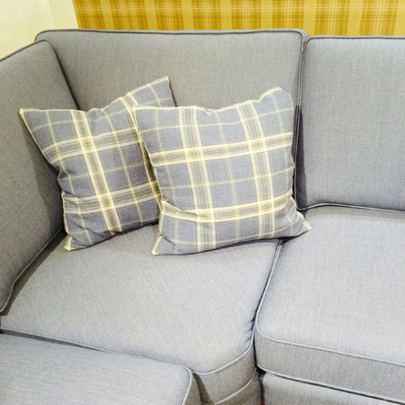 home furniture: Checked cushions on gray sofa. Modern furniture.