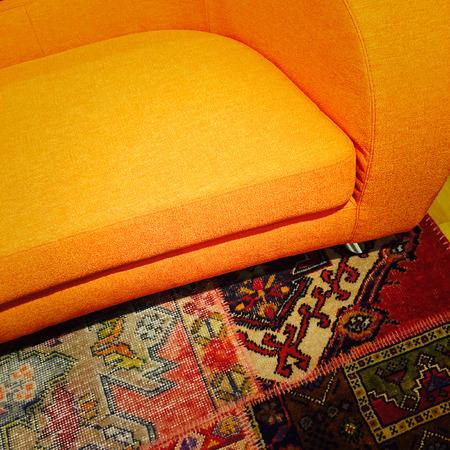 oriental rug: Bright orange sofa on colorful carpet. Modern furniture. Stock Photo