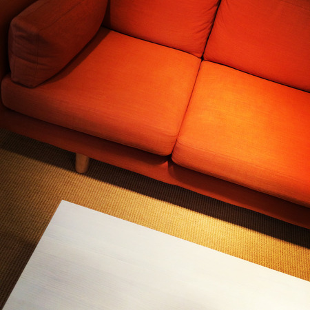 Bright orange sofa and coffee table. Living room detail. photo