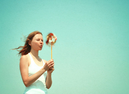 text free space: Young woman with a colorful pinwheel, retro styled image, paper texture. Stock Photo