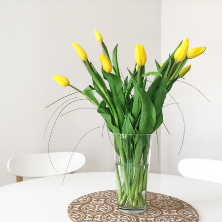 decor: Bouquet of fresh yellow tulips on a table. Home decor.