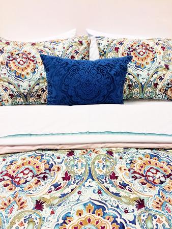 bedlinen: Close-up of a bed. Colorful bed linen with floral design.