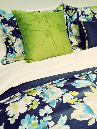 bedclothes: Close-up of a bed. Blue and green bed linen with floral design.