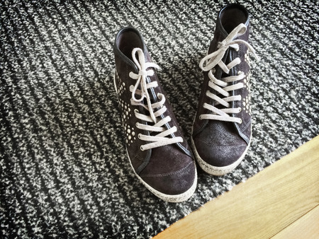 rivets: Fashionable shoes with metal rivets on gray striped carpet. Stock Photo