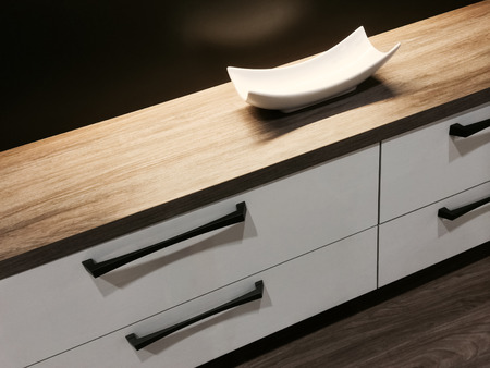 sleek: Chest of drawers with a decorative plate on its wooden surface. Stock Photo