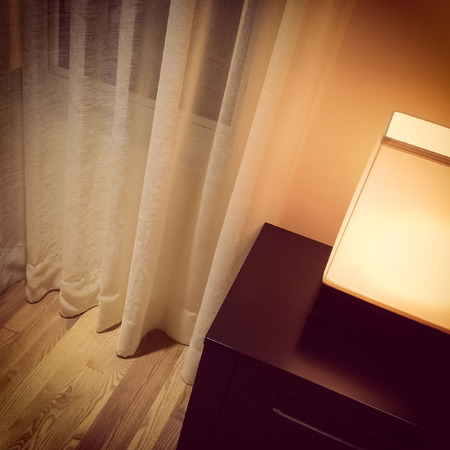 lamp shade: Cozy lamp in a room with white curtains. Modern design. Stock Photo